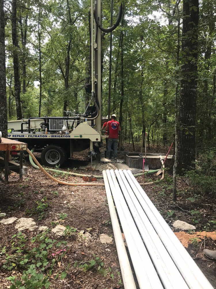 Driller Chris Adkison and helper Scott work on installing a well with their DM250 around Knoxville, Georgia.
